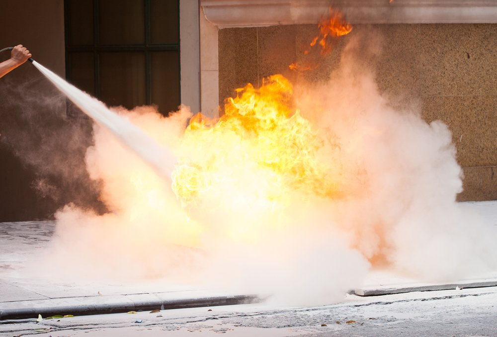 Fire-instructor showing how to use a fire extinguisher on a training fire