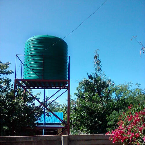 SS_A green water tank. Hoisted water tank. A water tower with green tank as the reservoir.