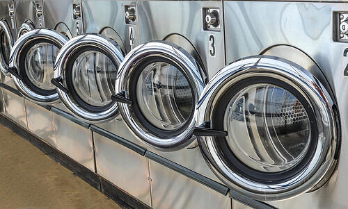 Row of industrial laundry machines in commercial laundry