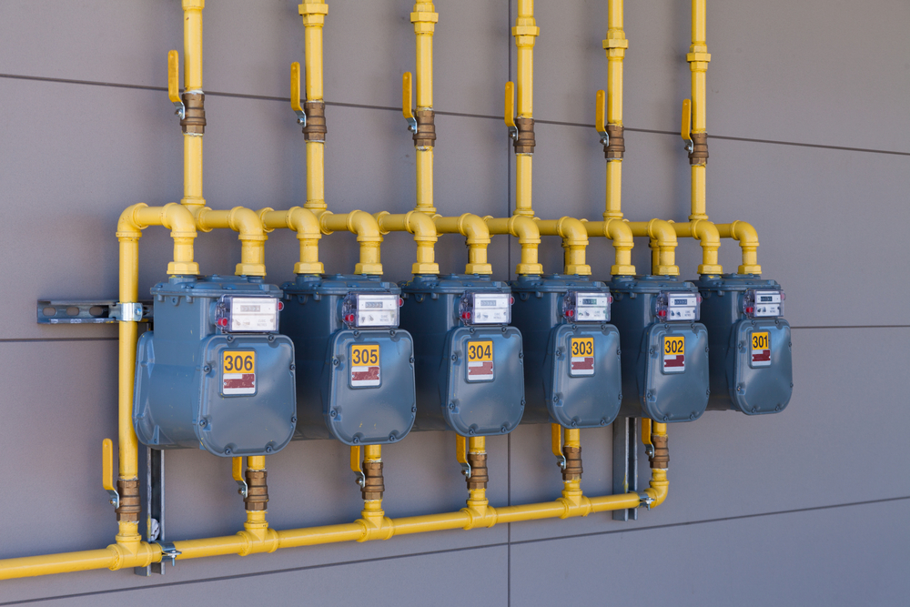 SS_Row of residential natural gas meters and yellow pipe plumbing on exterior wall to measure household energy consumption
