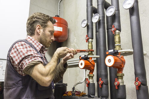 Plumber installing a circulation pump for energy conservation