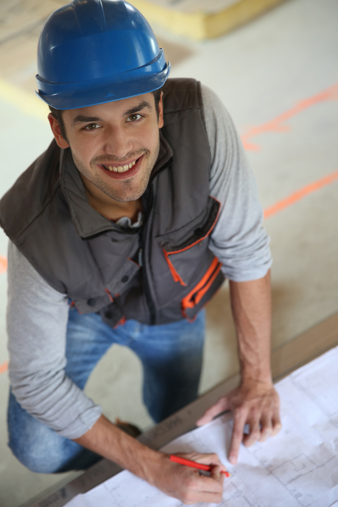 Construction worker checking blueprint
