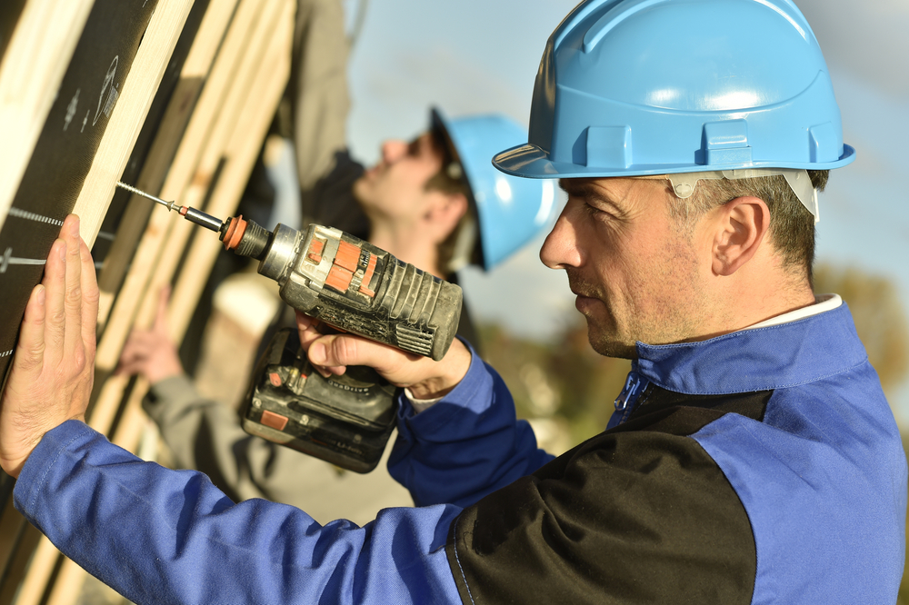 Construction worker using electric drill on building site