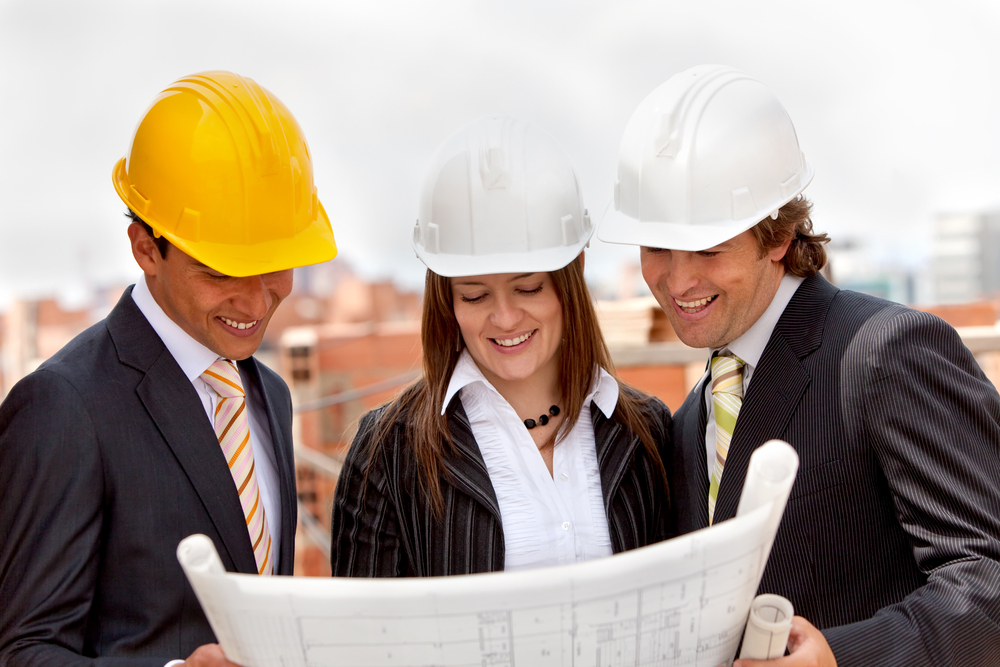 Group of architects at a construction site looking at the blueprints