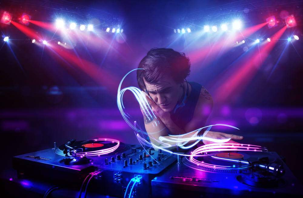 Handsome disc jockey playing music with light beam effects on stage-1