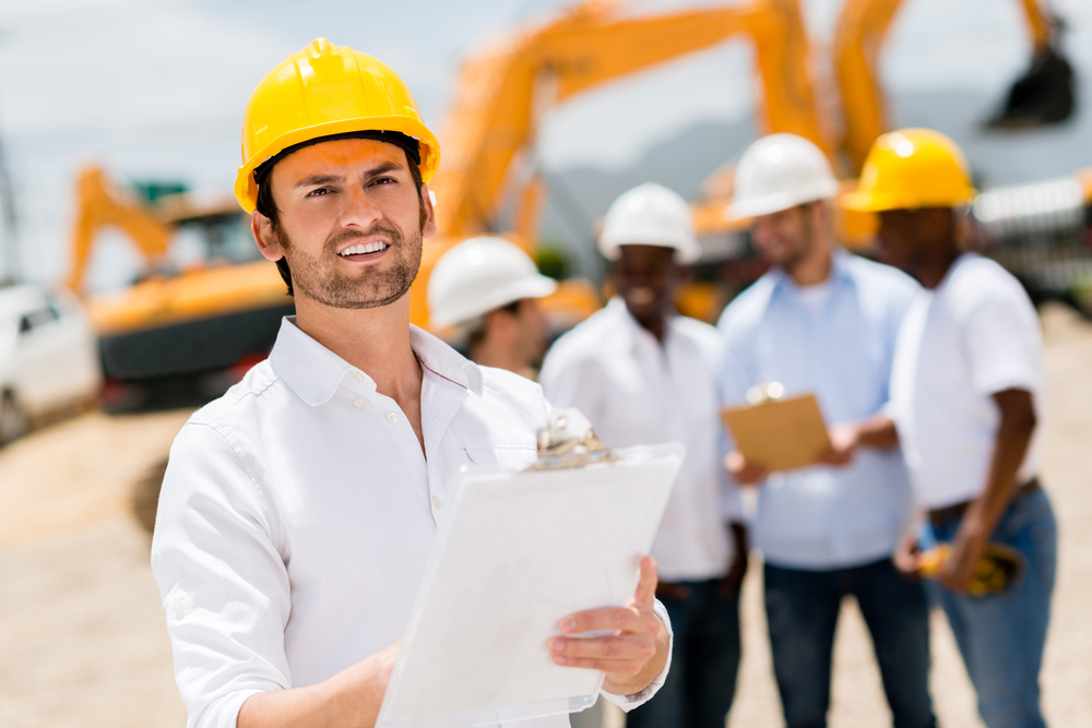 Male architect at a building site holding clipboard-1