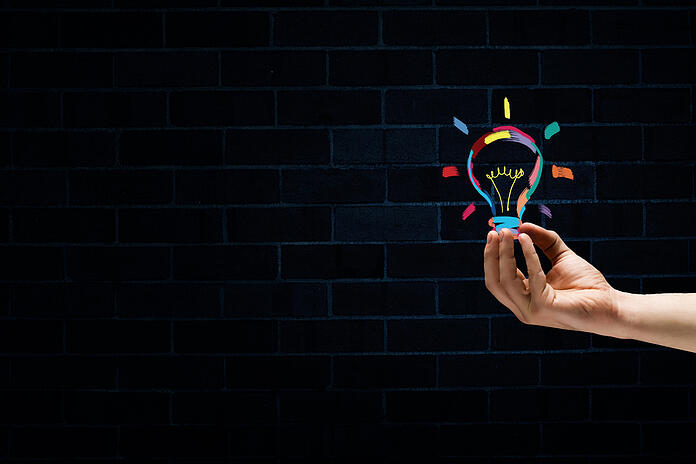 Male hand on dark background showing drawn light bulb-1