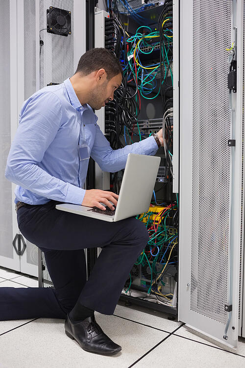 Man fixing wires while doing maintenance with laptop in data center