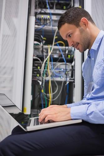 Man using laptop beside servers in data center