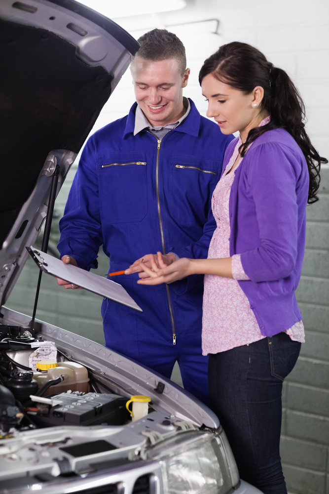 Mechanic standing next to a client in a garage