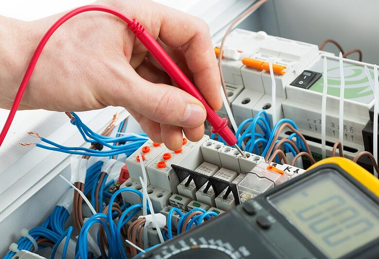 shutterstock_electrician uses multimeter probe at electrical switchgear cabinet