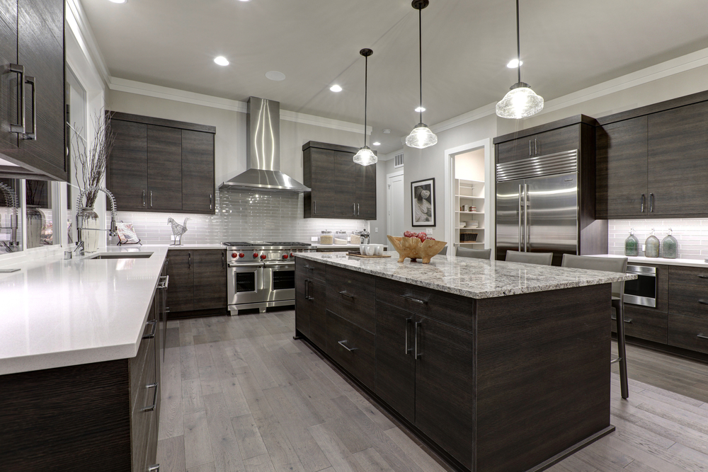 Modern gray kitchen features dark gray flat front cabinets paired with white quartz countertops and a glossy gray linear tile backsplash